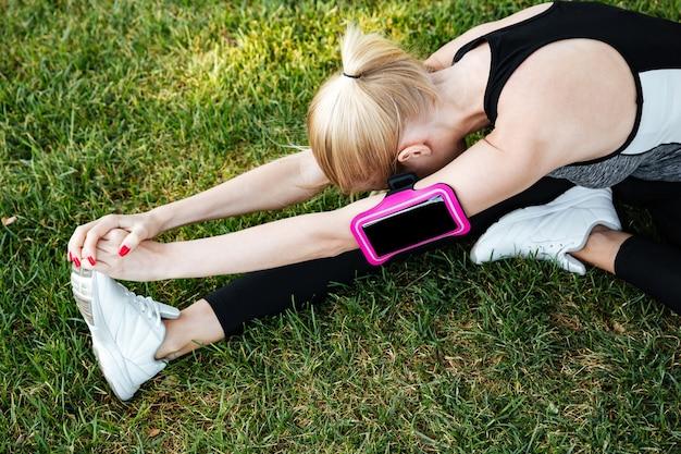 Młoda kobieta biegaczka rozciągająca nogi na świeżym powietrzu w parku