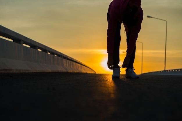 Młoda kobieta biegaczka wiążąca sznurowadła