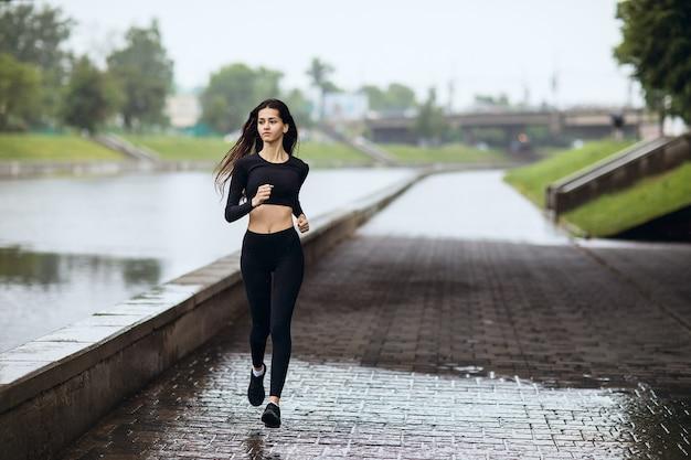 Młoda kobieta bieganie na nasypie podczas deszczu