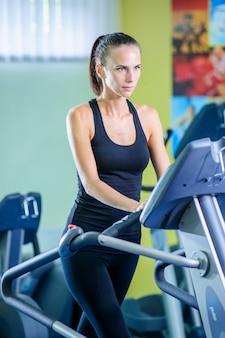 Młoda kobieta biegnie na bieżni