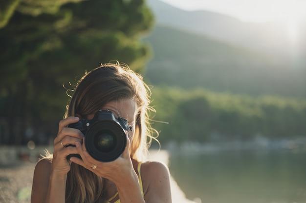 Młoda kobieta bierze fotografię bezpośrednio przy kamerą