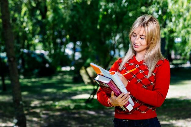 Młoda kobieta bierze notatki w ogródzie
