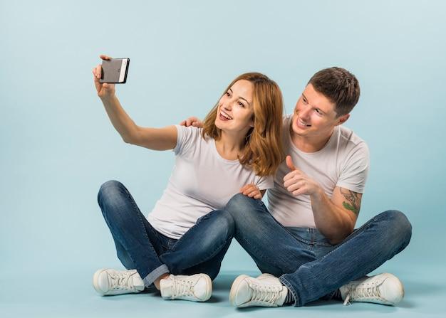 Młoda kobieta bierze selfie z jej chłopakiem pokazuje kciuk up podpisuje
