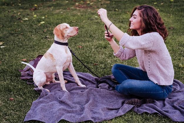 Młoda kobieta bierze selfie z telefonem komórkowym z jej psem przy parkiem