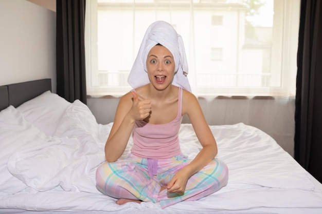 Młoda kobieta bierze tabletki przeciwbólowe, siedząc w domu na łóżku