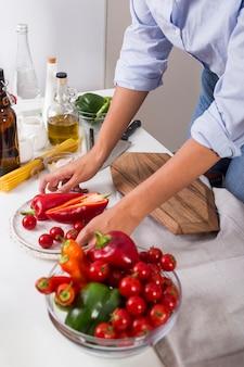 Młoda kobieta bierze talerza czerwony dzwonkowy pieprz i czereśniowi pomidory