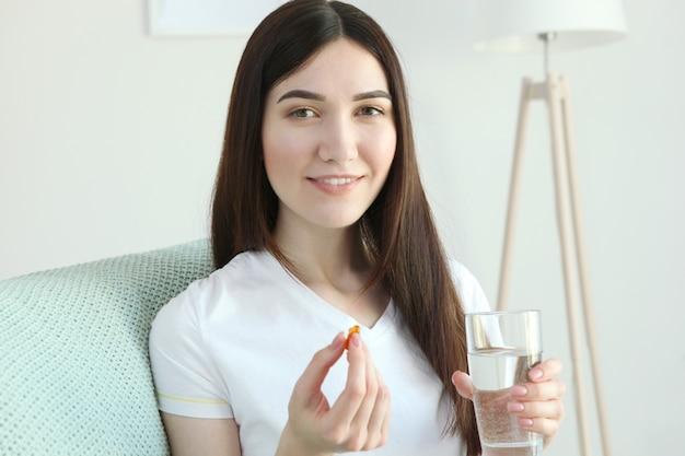 Młoda kobieta bierze w domu kapsułki z olejem rybim