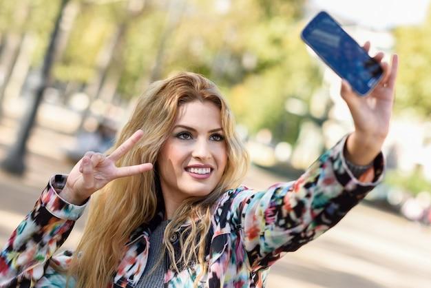 Młoda kobieta, biorąc autoportretów i pokazując gest zwycięstwa