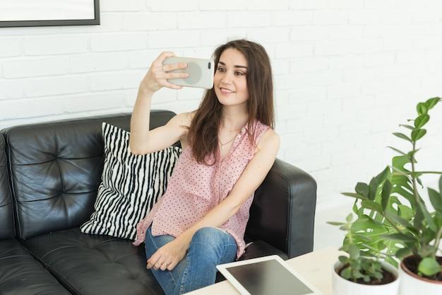 Młoda kobieta, biorąc selfie, siedząc na kanapie w domu