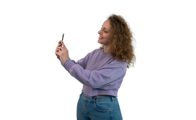 Młoda kobieta, biorąc selfie z jej smartfona na białym tle