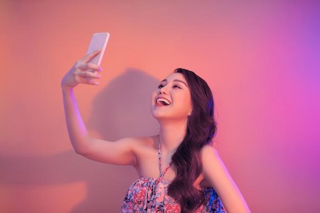 Młoda kobieta biorąc selfie zdjęcie na smartfonie patrząc aparat śmiejąc się szczęśliwy.