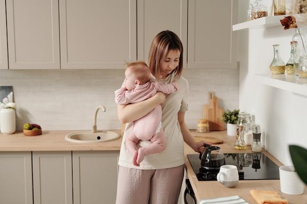Młoda kobieta biorąca czajnik z kuchenki elektrycznej