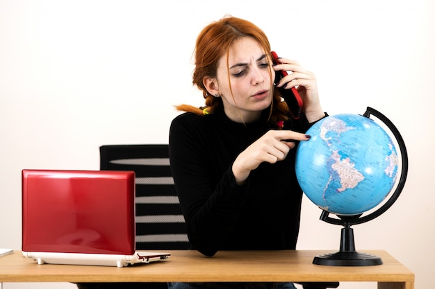 Młoda kobieta biura podróży kobieta siedzi za biurkiem z laptopa i geograficznej kuli ziemskiej świata rozmawia przez telefon komórkowy.