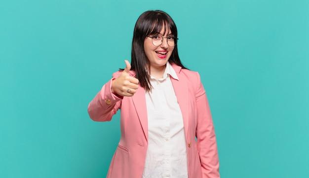 Młoda kobieta biznesu czuje się dumna, beztroska, pewna siebie i szczęśliwa, uśmiechając się pozytywnie z kciukami w górę