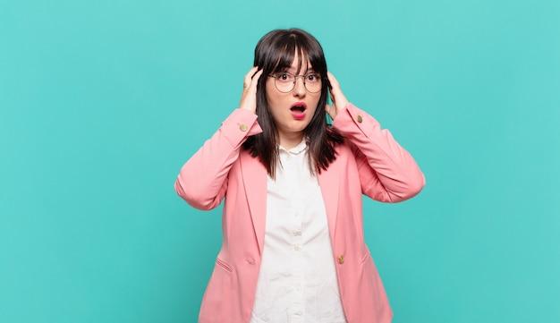 Młoda kobieta biznesu czuje się przerażona i zszokowana, podnosi ręce do głowy i panikuje z powodu błędu