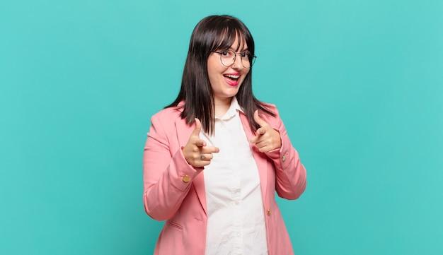 Młoda kobieta biznesu czuje się szczęśliwa, fajna, zadowolona, zrelaksowana i odnosząca sukcesy, wskazując na kamerę, wybierająca ciebie