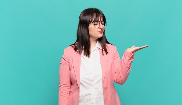 Młoda kobieta biznesu czuje się szczęśliwa i uśmiecha się od niechcenia, patrząc na przedmiot lub koncepcję trzymaną na dłoni z boku
