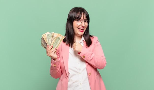 Młoda kobieta biznesu czuje się szczęśliwa, pozytywna i odnosząca sukcesy, zmotywowana, gdy staje przed wyzwaniem lub świętuje dobre wyniki