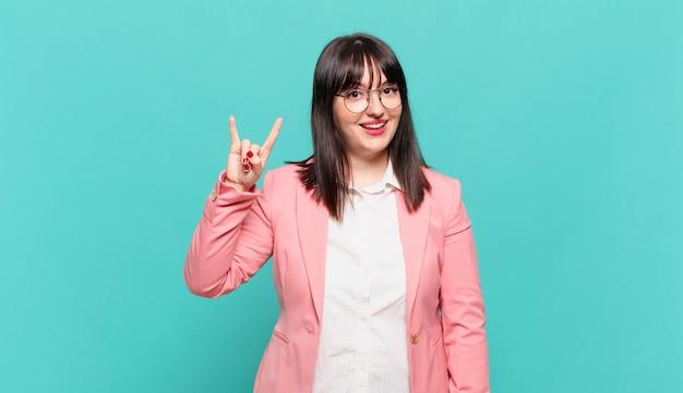 Młoda kobieta biznesu czuje się szczęśliwa, zabawna, pewna siebie, pozytywna i buntownicza, wykonując ręką rockowy lub heavy metalowy znak