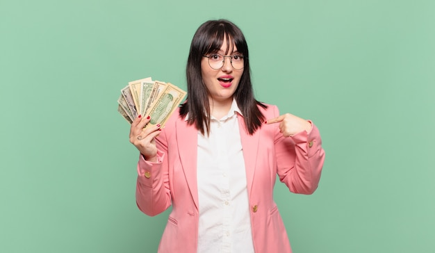 Młoda kobieta biznesu czuje się szczęśliwa, zaskoczona i dumna, wskazując na siebie z podekscytowanym, zdziwionym spojrzeniem
