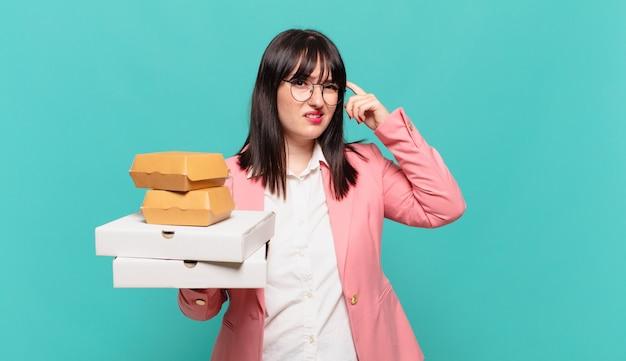 Młoda kobieta biznesu czuje się zdezorientowana i zdezorientowana, pokazując, że jesteś szalony, szalony lub oszalały