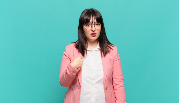 Młoda kobieta biznesu czuje się zdezorientowana, zakłopotana i niepewna, wskazując na siebie, zastanawiając się i pytając, kto, ja?