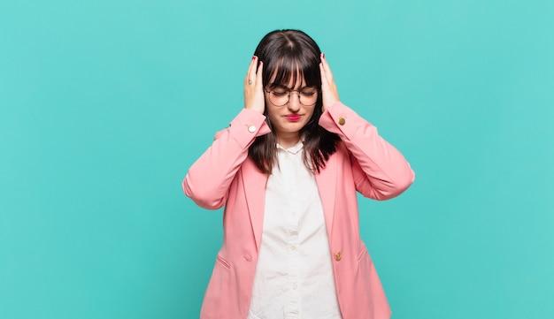 Młoda kobieta biznesu czuje się zestresowana i sfrustrowana, podnosi ręce do głowy, czuje się zmęczona, nieszczęśliwa i z migreną