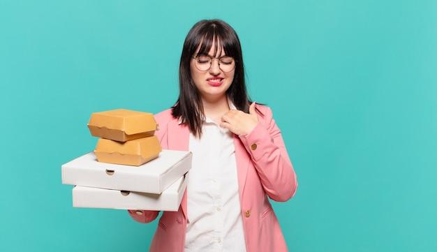Młoda kobieta biznesu czuje się zestresowana, niespokojna, zmęczona i sfrustrowana, ciągnie za koszulkę, wygląda na sfrustrowaną problemem