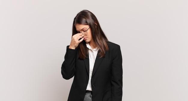 Młoda kobieta biznesu czuje się zestresowana, nieszczęśliwa i sfrustrowana, dotyka czoła i cierpi na migrenę lub silny ból głowy