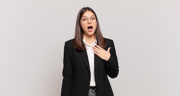 Młoda kobieta biznesu czuje się zszokowana i zaskoczona, uśmiecha się, bierze rękę do serca, jest szczęśliwa, że jest tą jedyną lub okazuje wdzięczność