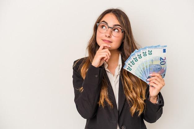 Młoda kobieta biznesu kaukaski gospodarstwa banknotów na białym tle patrząc w bok z wyrazem wątpliwości i sceptyczny.