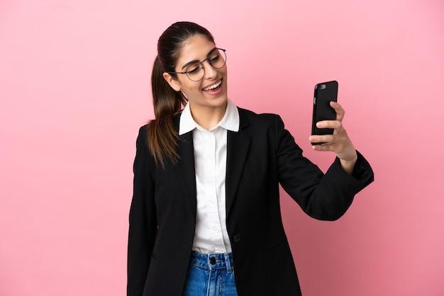 Młoda kobieta biznesu kaukaski na białym tle na różowym tle robi selfie