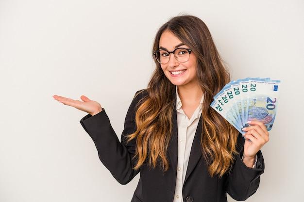 Młoda kobieta biznesu kaukaski trzymając banknoty na białym tle na białym tle pokazujące miejsce na dłoni i trzymając inną rękę na pasie.