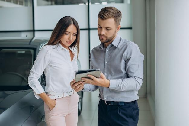Młoda kobieta biznesu kupująca samochód w salonie samochodowym