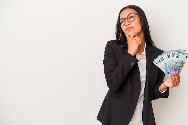 Młoda kobieta biznesu łacińskiego gospodarstwa rachunki kawa na białym tle patrząc w bok z wyrazem wątpliwości i sceptyczny.