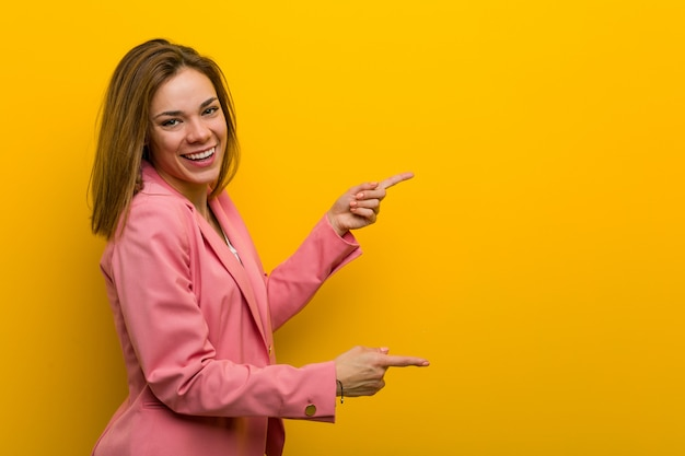 Młoda kobieta biznesu mody podekscytowany, wskazując palcami z dala.