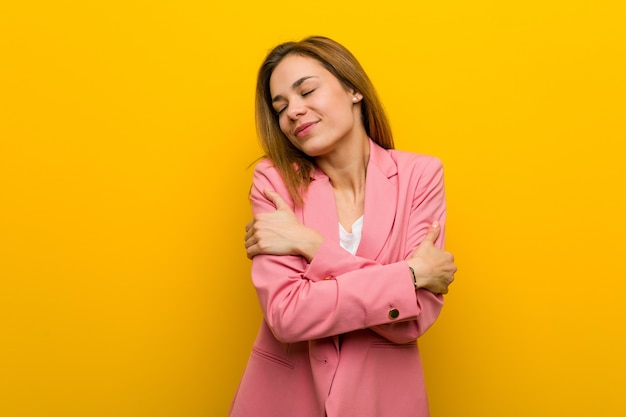 Młoda kobieta biznesu mody przytula się, uśmiechając się beztrosko i szczęśliwie.
