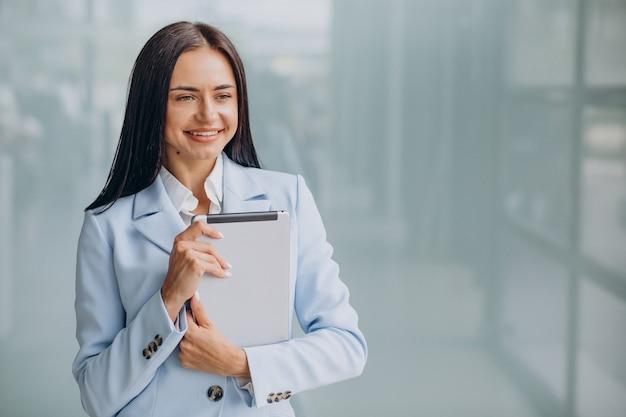 Młoda kobieta biznesu na białym tle trzymając tablet