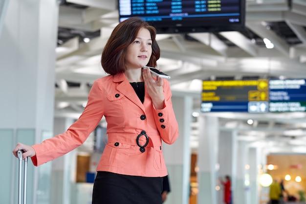 Młoda kobieta biznesu na lotnisku z bagażem, nagrywa wiadomość audio na telefon i uśmiecha się.