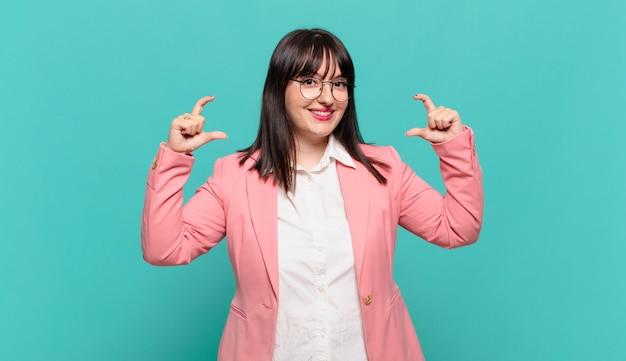 Młoda kobieta biznesu oprawiająca lub zarysowująca własny uśmiech obiema rękami, wyglądająca pozytywnie i szczęśliwie, koncepcja wellness