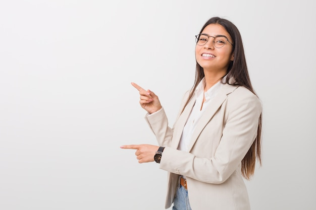 Młoda kobieta biznesu podekscytowany, wskazując palcami daleko
