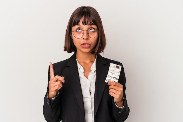 Młoda kobieta biznesu rasy mieszanej gospodarstwa pigułki na białym tle wskazując do góry z otwartymi ustami.