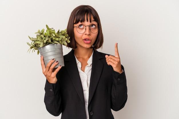 Młoda kobieta biznesu rasy mieszanej gospodarstwa roślin na białym tle wskazując do góry z otwartymi ustami.