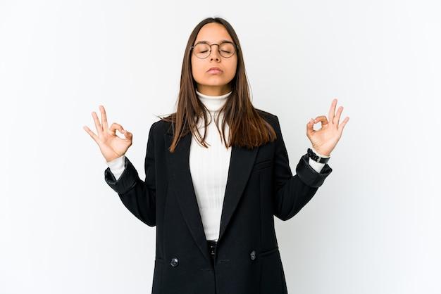 Młoda kobieta biznesu rasy mieszanej na białym relaksuje po ciężkim dniu pracy, wykonuje jogę.