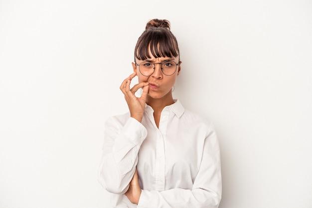 Młoda kobieta biznesu rasy mieszanej na białym tle z palcami na ustach zachowując tajemnicę.
