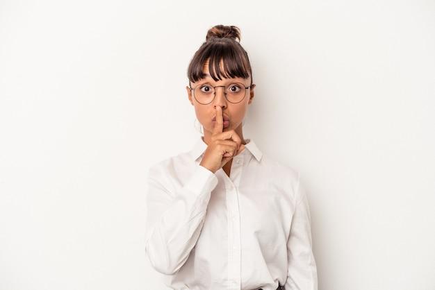 Młoda kobieta biznesu rasy mieszanej na białym tle zachowując tajemnicę lub prosząc o ciszę.