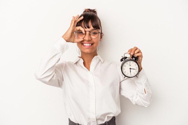 Młoda kobieta biznesu rasy mieszanej trzyma budzik na białym tle podekscytowany, trzymając ok gest na oko.