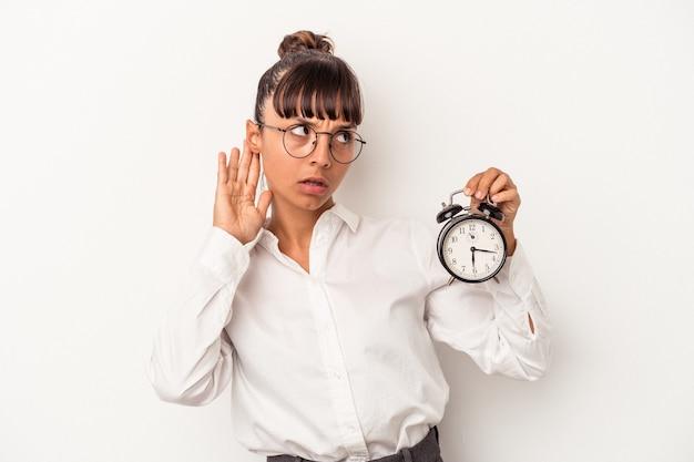 Młoda kobieta biznesu rasy mieszanej trzyma budzik na białym tle próbuje słuchać plotek.
