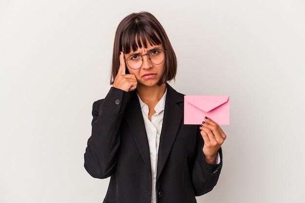 Młoda kobieta biznesu rasy mieszanej trzyma list na białym tle wskazując świątynię palcem, myśląc, koncentruje się na zadaniu.