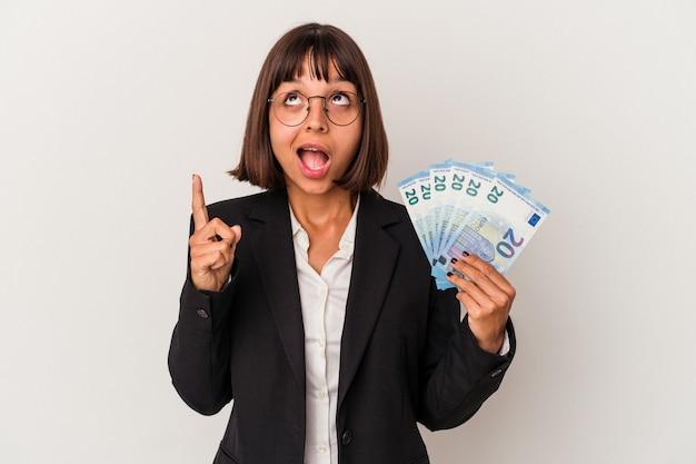 Młoda kobieta biznesu rasy mieszanej trzymając banknoty na białym tle wskazujące do góry z otwartymi ustami.